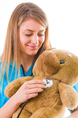 medical procedure: Beautiful young pediatrician presenting medical procedure with the help of a teddy bear in a fun way.