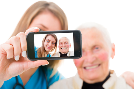 to ensure: Young nurse taking a selfie to ensure the family about the good condition of the grandmother.