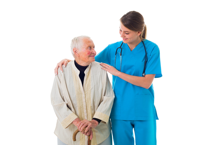 infirm: Beautiful young nurse supporting a sick elderly woman. Stock Photo
