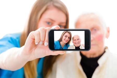 conexiones: Enfermera joven que toma una selfie para asegurar a la familia sobre el buen estado de la abuela. Foto de archivo