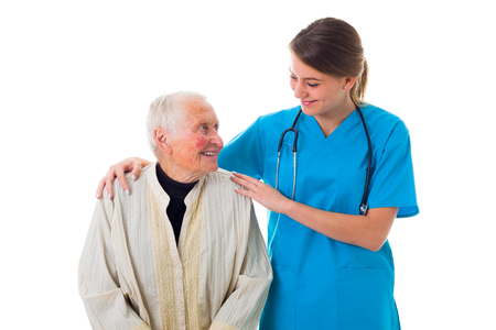 Attentive and caring young nurse supporting a sick elderly woman.