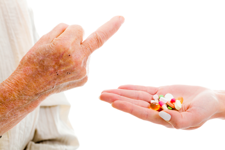 middle aged women: Elderly woman refusing medications with a rude gesture. Stock Photo