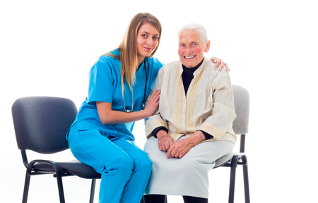 aiding: Doctor and elderly patient sitting on chairs and talking.