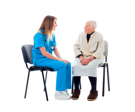 alzheimers: Doctor and elderly patient sitting on chairs and talking.