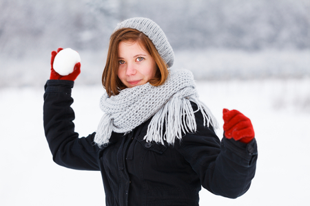 boule de neige: Jolie fille avec les cheveux rouges préparation de jeter boule de neige. Banque d'images