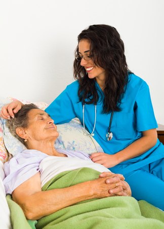 assisting: Kind nurse easing elderly ladys days in nursing home with care help and joy.