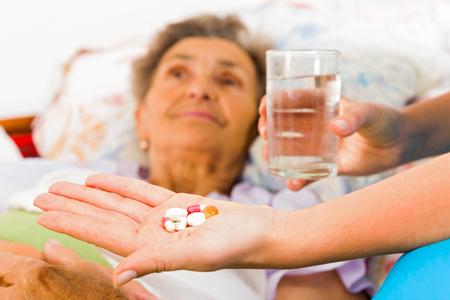 Verpleegkundige het geven van medicatie aan bejaarde patiënt in verpleeghuis.