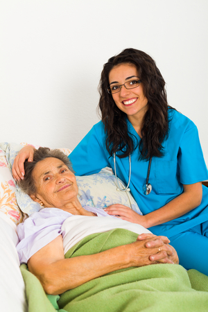 caring for: Nurse caring for sick elder lady in nursing home. Stock Photo