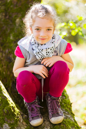 climbed: Cute little girl sitting on a three that she climbed on otdoors in the countryard.