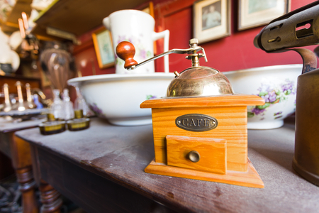 antique shop: Old wooden dusty cofee grinder on a wooden table in an antique shop. Stock Photo