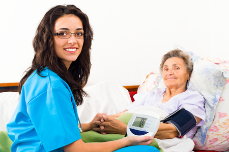 Kind nurse measuring elderly patient's blood pressure at home.