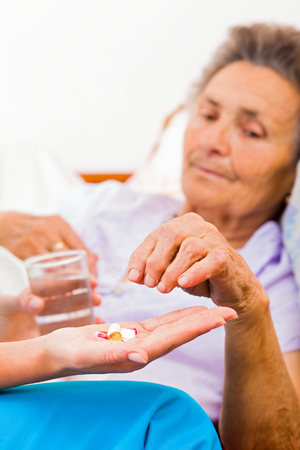 Elderly woman taking pills with glass of water.