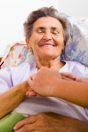 hand care: Caring nurse holding kind elderly ladys hands in bed. Stock Photo