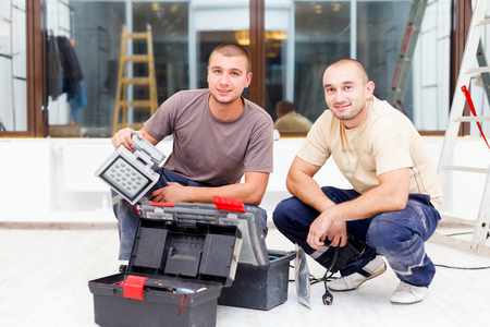 teammate: Teammate electricians with their tool boxes working in homes.