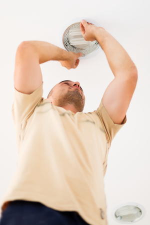 mounting: Last step in mounting a light by an electrician. Stock Photo