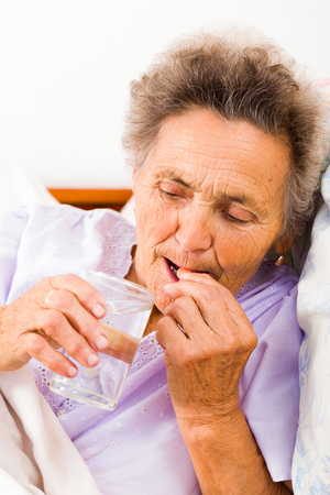 disease patients: Elderly lady taking pills with glass of water at home.