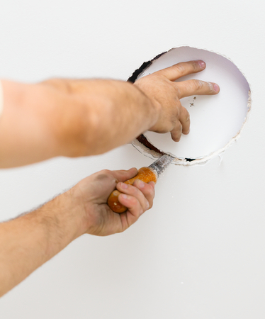 ceiling: First step in installing ecological light in ceiling by electrician - cutting hole.