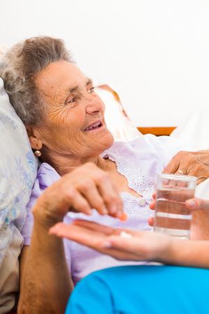 personas ayudando: Mujer mayor que toma píldoras con un vaso de agua. Foto de archivo