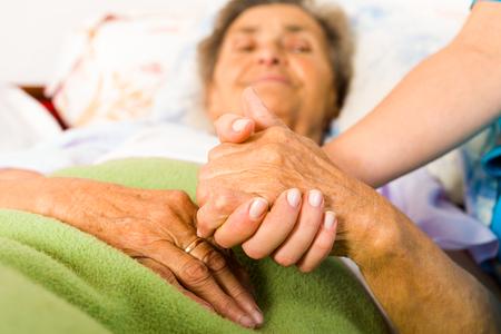 保健医療看護師は、思いやりのある態度と高齢者の女性の手を握ってします。