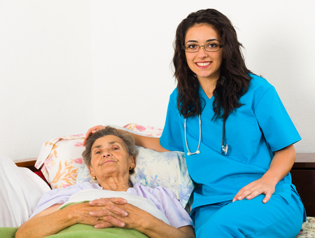 nursing assistant: Smiling nurse caring for kind elder patient in nursing home.