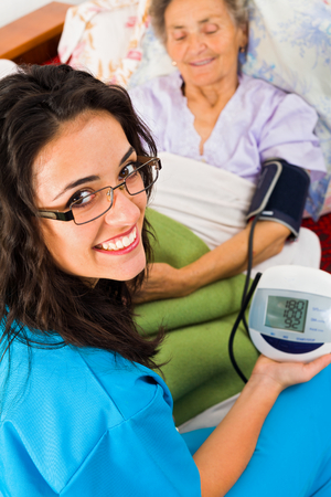 Doctor measuring blood pressure in nursing home with digital device. Banco de Imagens