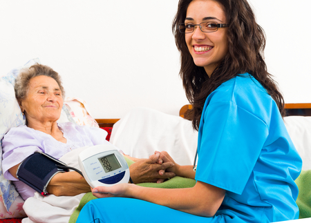 home care nurse: Nurse using digital blood pressure for senior patient.