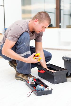 herramientas de construccion: Manitas buscar en su caja de herramientas para las herramientas necesarias. Foto de archivo