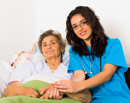 patients: Happy joyful nurses caring for kind elderly patients helping their days in nursing home. Stock Photo