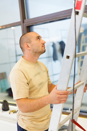 teammate: Electrician man helping his teammate on ladder.