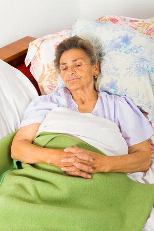 disease patients: Serene senior woman saying prayers in bed before going to sleep. Stock Photo