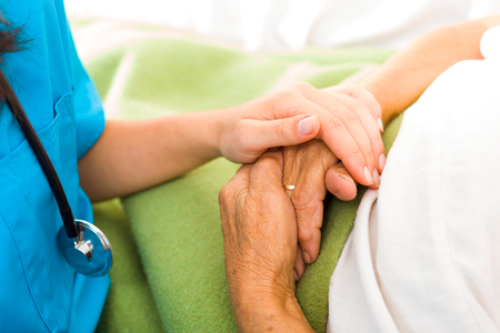 nursing assistant: Care help love and trust to elderly people - holding hands.