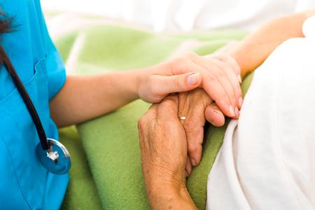 pielęgniarki: Troska pomocy miłość i zaufanie do osób starszych - trzymając się za ręce. Zdjęcie Seryjne