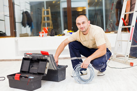 necessary: Handyman searching in his tool box for the necessary tools.