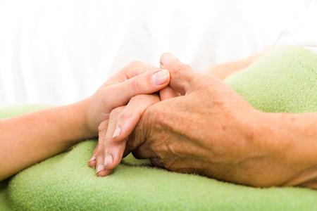 pacientes: Enfermera de atención de la salud el cuidado de ancianos concepto - tomados de la mano. Foto de archivo