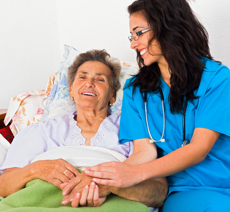 Kind nurse easing elderly ladys days in nursing home with care help and joy.