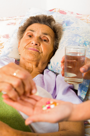 Supplements in nurse's hands for weak senior woman. photo