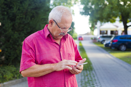 unknowing: Elderly man using smartphone on streets paying attention.