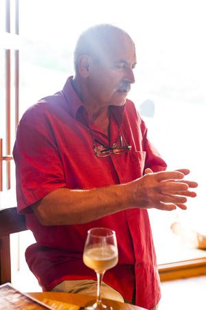 drunk test: Senior man talking with pathos next to a glass of white wine.