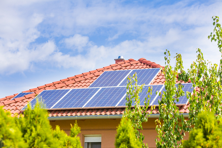 alternative energy: Solar panel cells on the roof of a new house agains blue sky. Stock Photo