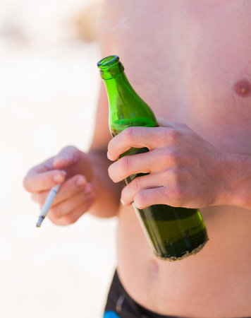 hold on: Man holding alcohol and cigarette, both bad for health. Stock Photo