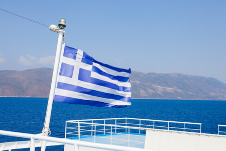 ferryboat: Greek flag on Cephalonian ferry - the main land in background. Stock Photo