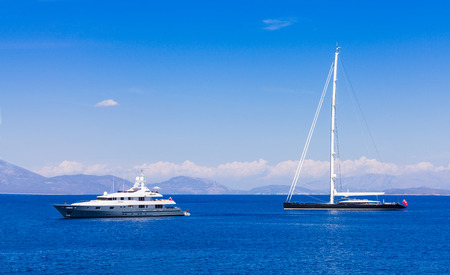 yacht people: Two different types of yachts in the ocean: a motorized luxury yacht and one hybrid (sailing and motorized) cruising yacht.