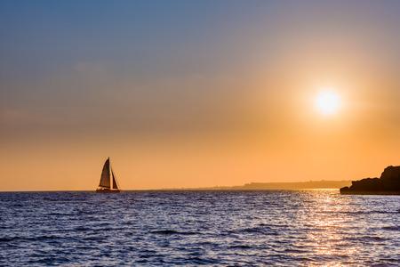 voilier ancien: Distant voile yacht à travers l'horizon au coucher du soleil.