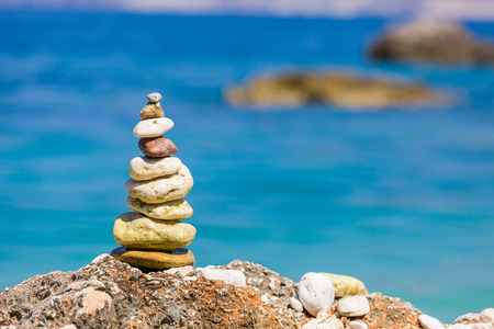A pile of a well balanced rocks on the beach usable for simple backgrounds or balance and meditation concepts. Stock Photo