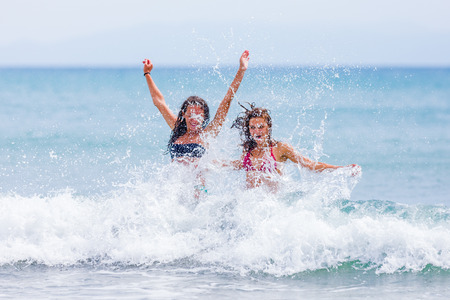 sea wave: Two brunette women with suntan splashed by the waves of the mediterranean sea. Stock Photo
