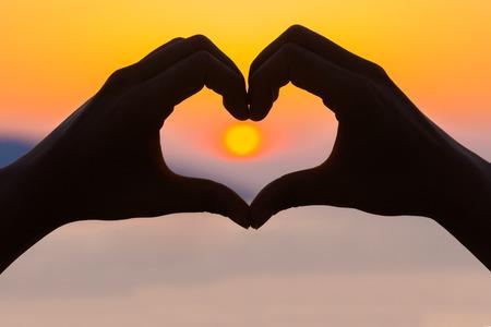 haciendo el amor: Mujeres manos haciendo una forma de corazón en la puesta del sol - la salud, el concepto de amor.