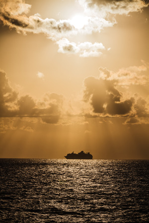 mediterranian: Light rays penetrating the clouds above a big cruiser ship in the Mediterranean sea.