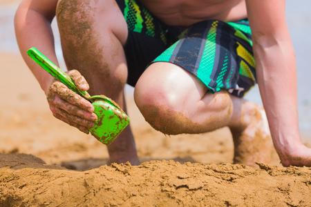 manos sucias: persona de sexo masculino con las manos sucias y los pies jugando en la arena de una sowel. Foto de archivo