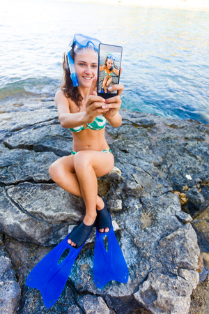 flippers: Girl in swimming suit and snorkeling gear taking a selfie with a smartphone on rock in Greece at the sea.