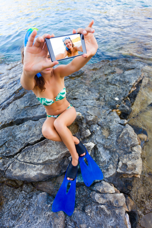 shores: Pretty youn woman taking a selfie in snorkeling equipment on the rocky shores of the Mediterranean sea.
